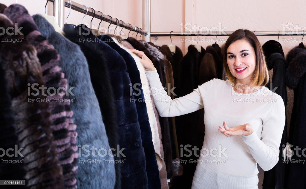 8d98672861f4 mulher escolhendo o melhor casaco de peles em loja de roupas femininas foto  de stock royalty