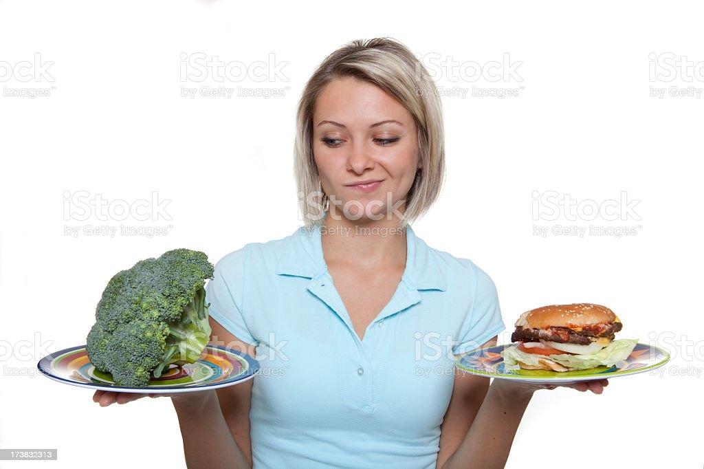 Woman choosing between a broccoli and a hamburger royalty-free stock photo