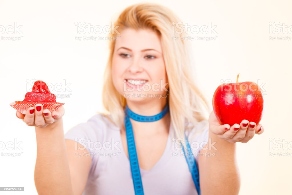 Woman choosing between apple and sweet cupcake royalty-free stock photo