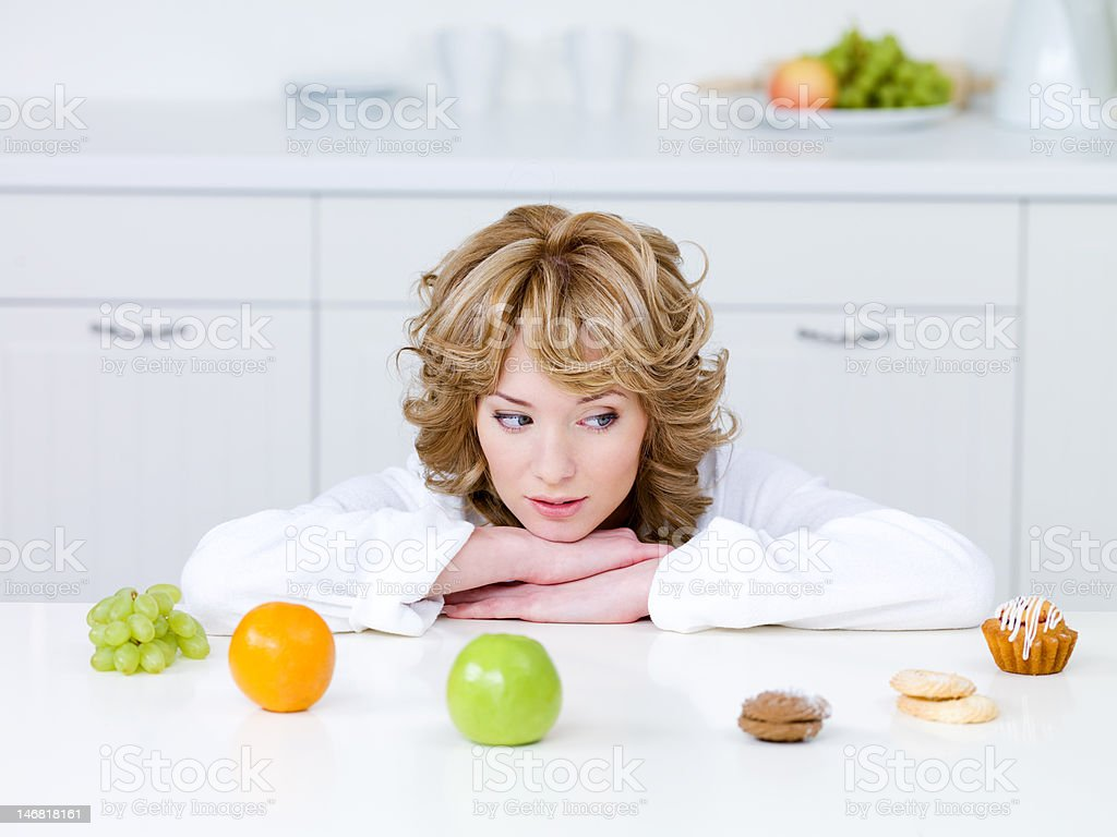 Woman choosing between fruits and cakes stock photo