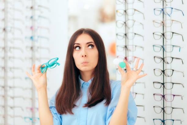 frau die wahl zwischen brille und kontaktlinsen in optik shop - lieblingsrezepte stock-fotos und bilder