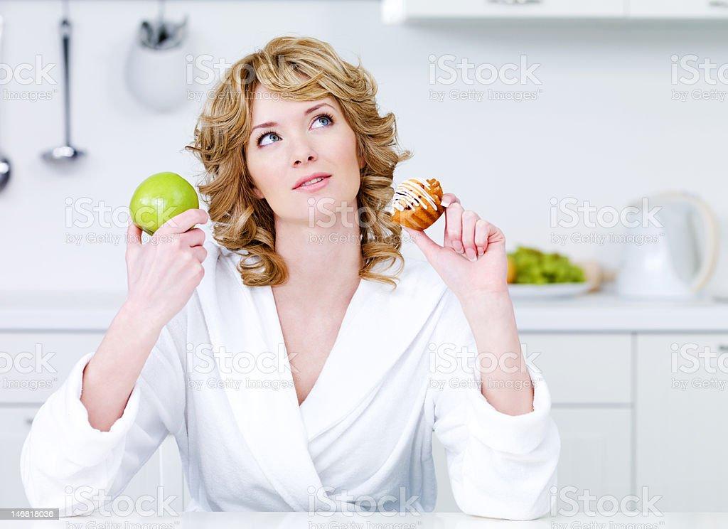 Woman choosing between healthy food and caloric cake royalty-free stock photo