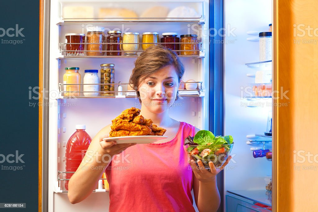 Woman Choosing Between Healthy or Unhealthy Snack by Open Refrigerator stock photo