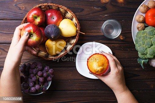 istock Woman choosing between junk food and fruits 1050035358