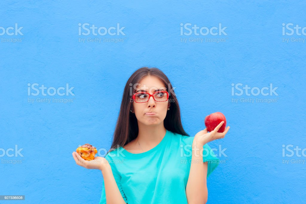 Woman Choosing Between Unhealthy Muffin and Healthy Apple stock photo