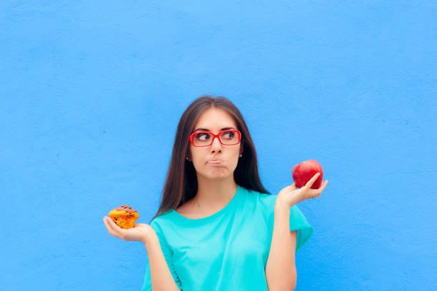 Mujer eligiendo entre insalubre Muffin manzana sana - foto de stock