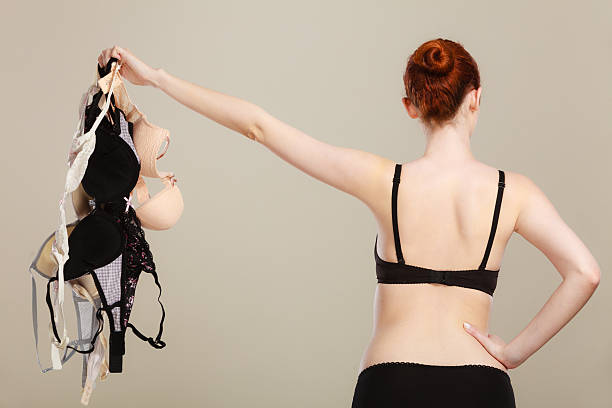 woman choosing bras to wear Bosom concept. Slim attractive red hair woman wearing black underwear holding many bras in hand, choosing witch bra to wear, rear view bra stock pictures, royalty-free photos & images