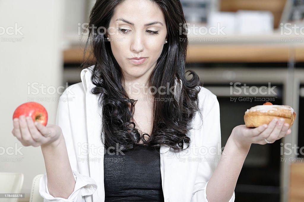 Woman choosing cake or fruit stock photo