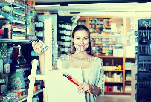istock woman choosing canvas on easel 587545466