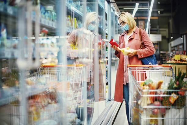 mulher escolhendo queijo no supermercado. - comida congelada - fotografias e filmes do acervo