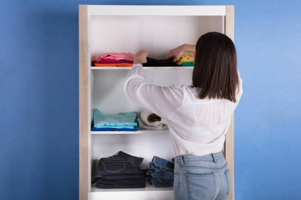 Woman Choosing Cloth From Shelf Rear View Of A Young Woman Choosing Cloth From Shelf arrangement stock pictures, royalty-free photos & images