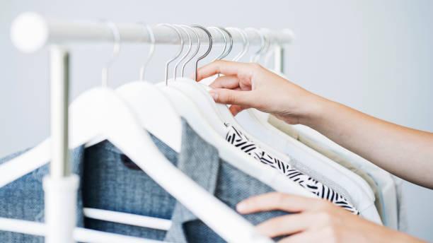mujer escogiendo ropa en un estante - vestimenta fotografías e imágenes de stock