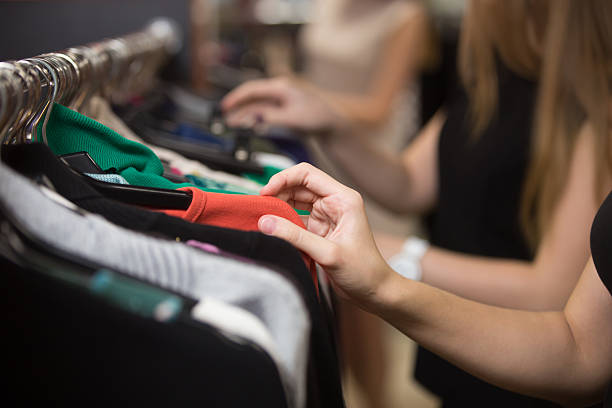 Woman choosing clothes on rack, closeup stock photo