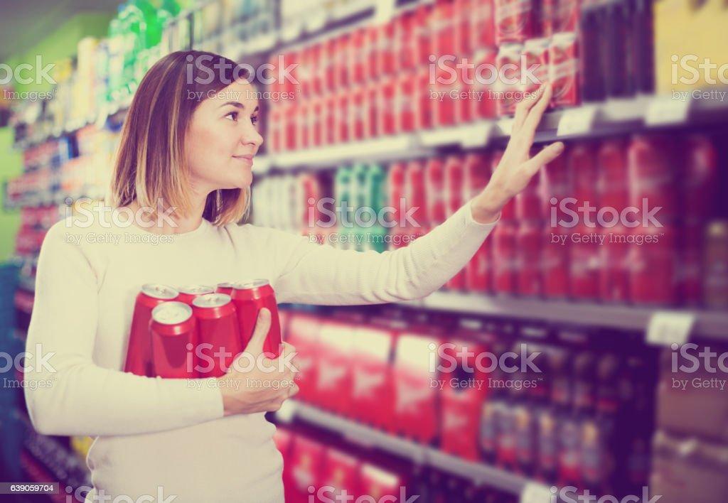 Woman choosing cold beer in supermarket
