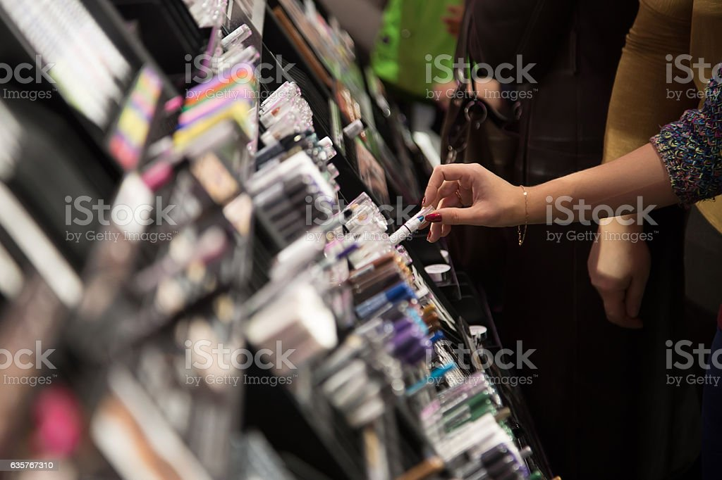 Woman Choosing color cosmetics in the store stock photo