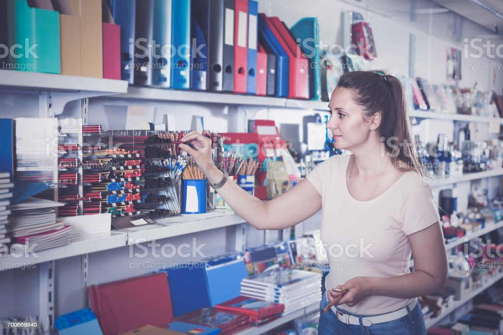 woman choosing color pencil, different color copybook in stationery shop stock photo
