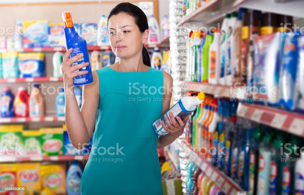 Woman choosing detergent for washing stock photo