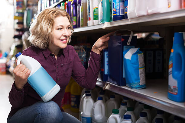 woman choosing detergent in shop - bleach stock pictures, royalty-free photos & images