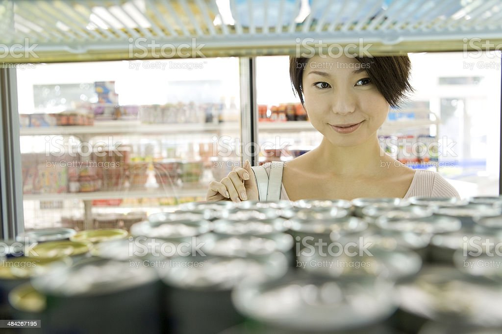 Woman choosing drink at convenience store stock photo