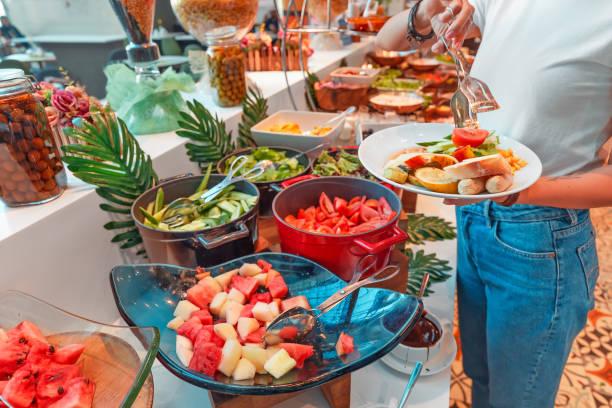 Woman choosing food in open buffet at breakfast in hotel stock photo