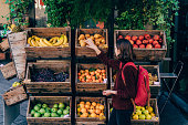 Young Caucasian woman choosing fresh fruits on the street of Florence