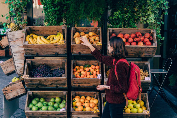 woman choosing fresh fruits on the street of florence - mercato frutta donna foto e immagini stock