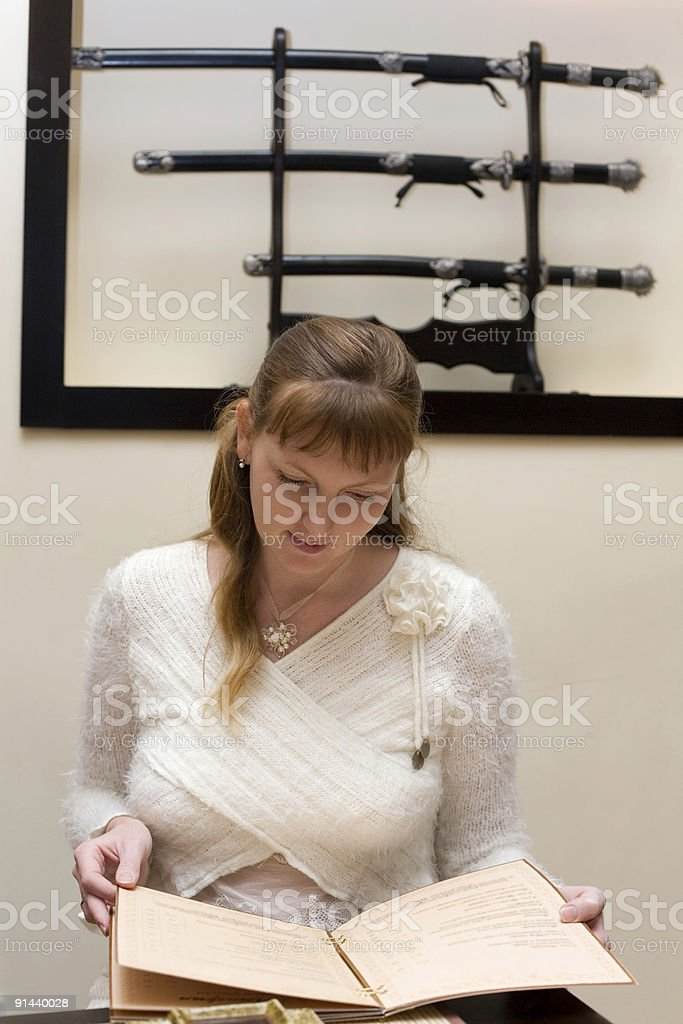 Woman choosing from menu in the japanese restaurant royalty-free stock photo