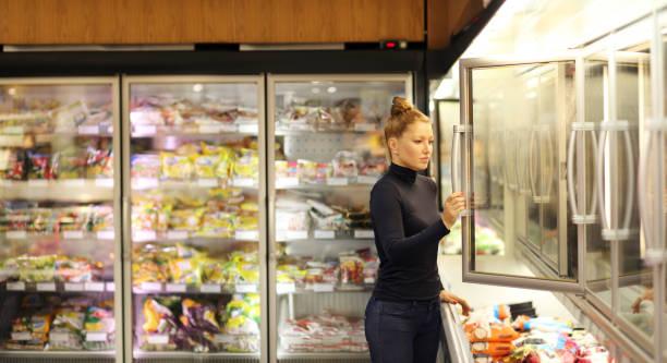 슈퍼마켓 냉장고에서 냉동 식품을 선택 하는 여자 - 냉동식품 뉴스 사진 이미지