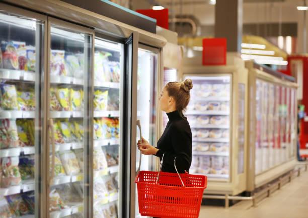 mulher que escolhe o alimento congelado de um congelador do supermercado - comida congelada - fotografias e filmes do acervo