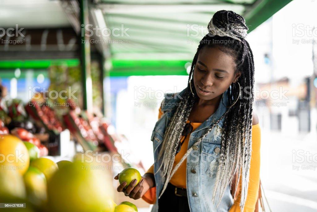 Vrouw vruchten op straatmarkt kiezen - Royalty-free 20-24 jaar Stockfoto