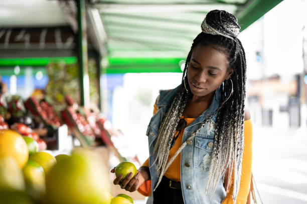 woman choosing fruits on street market - caribbean food stock photos and pictures