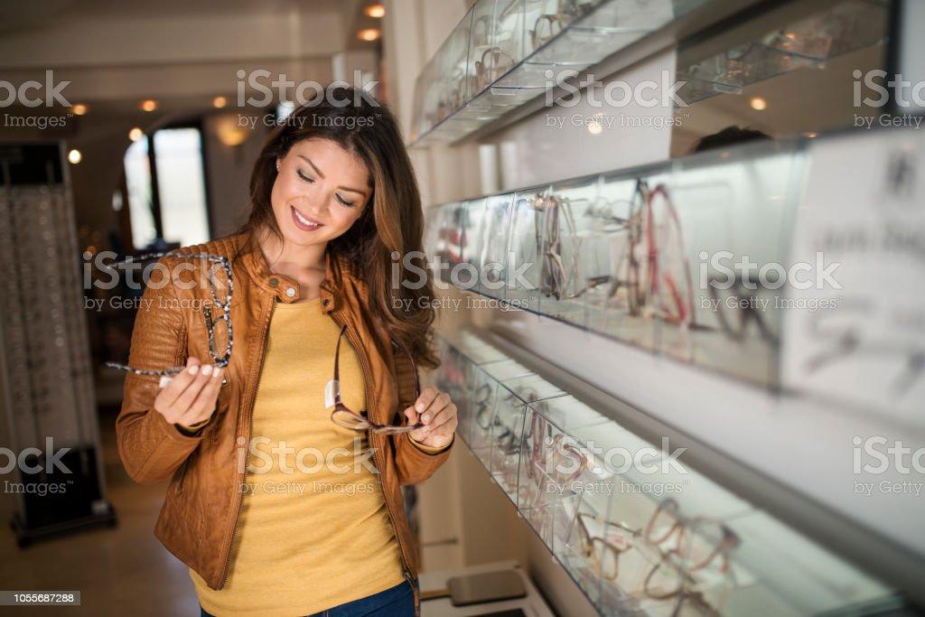 a7df0e4408c9cf Vrouw bril kiezen in optische winkel met spiegel royalty free stockfoto