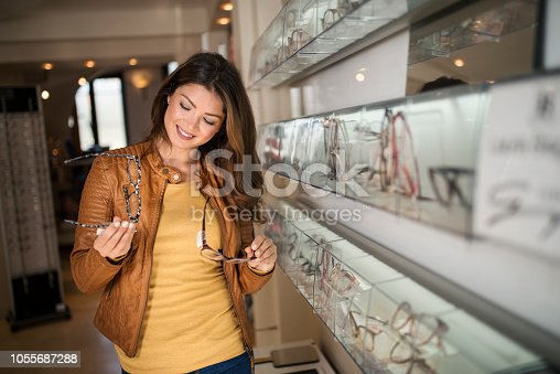 Woman choosing glasses in optical store using mirror