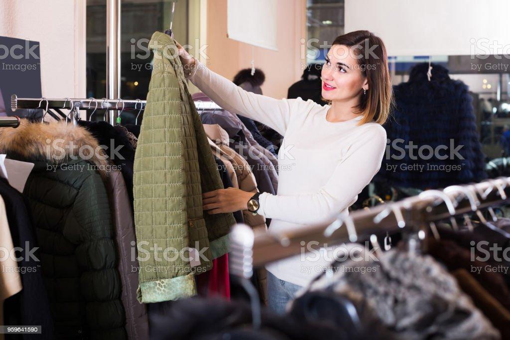 mujer elegir chaqueta acolchada verde en tienda de ropa de las mujeres - Foto de stock de 25-29 años libre de derechos