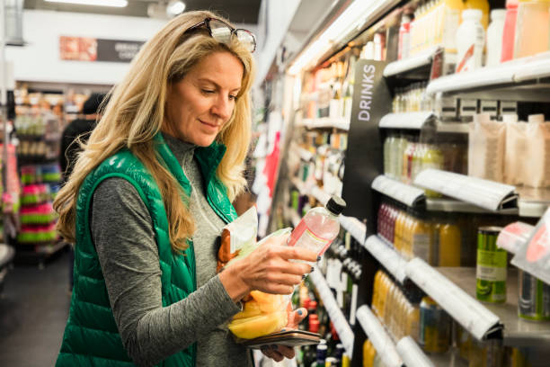 Woman Choosing Her Lunch A front-view shot of a mature caucasian woman standing in a supermarket, she is shopping for a healthy snack. real life stock pictures, royalty-free photos & images