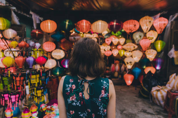 Woman choosing lanterns in Hoi An Young Caucasian woman  choosing lanterns in Hoi An night market stock pictures, royalty-free photos & images