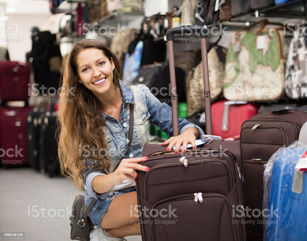 Woman choosing luggage bag in shop stock photo