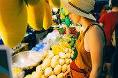 Woman choosing mango in Bangkok market, Thailand