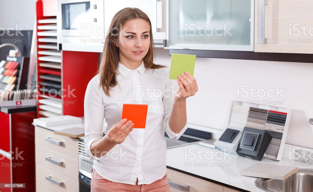 Woman choosing material for kitchen furniture stock photo