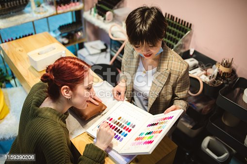 Woman choosing nail polish in beauty salon, looking at nail color palette, high angle view