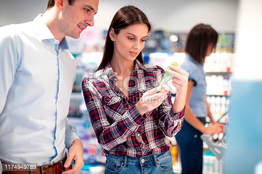 Woman holding bottle of shampoo and looking at the label with partner in pharmacy