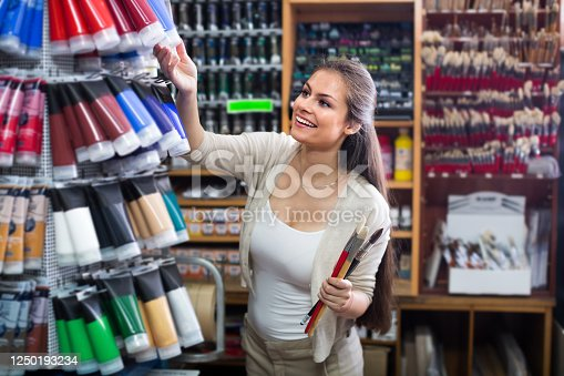 portrait of young cheerful woman choosing paint color in tube indoors