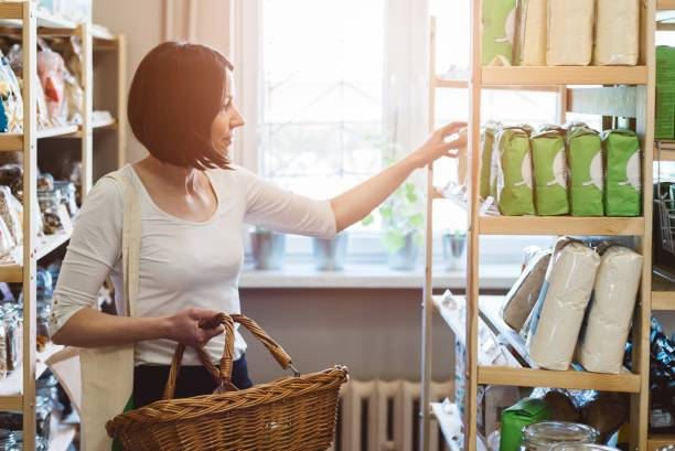 woman choosing products in ecological shop - consumer products stock pictures, royalty-free photos & images