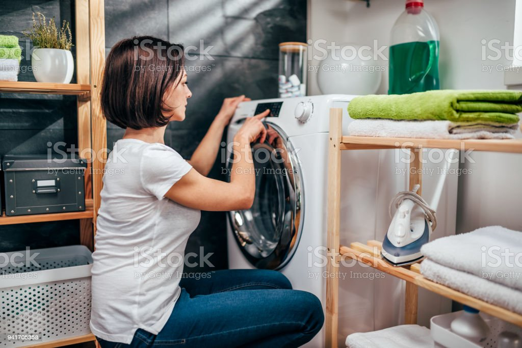 Woman choosing program on washing machine stock photo