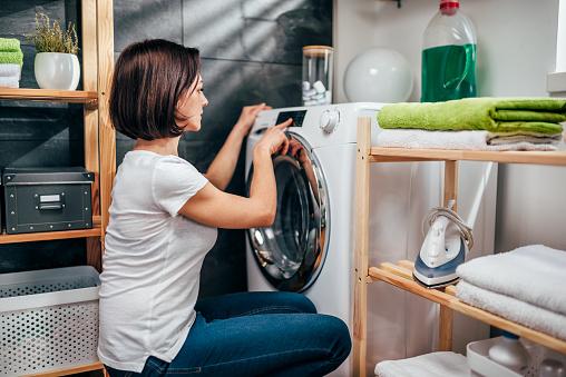 洗濯機にプログラムを選択する女性 - 1人のストックフォトや画像を多数ご用意