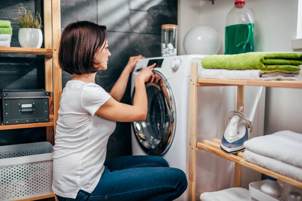 woman choosing program on washing machine - laundry laundry room stock pictures, royalty-free photos & images