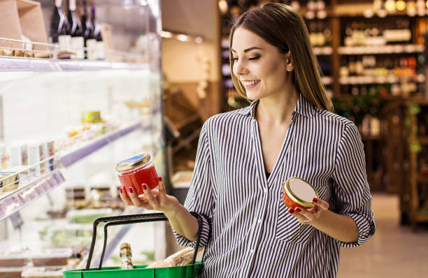 Woman choosing red caviar at fish supermarket stock photo