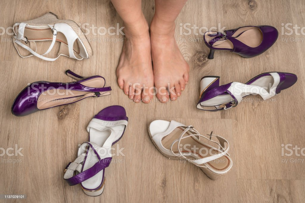 Young woman choosing shoes and many shoes on wooden floor
