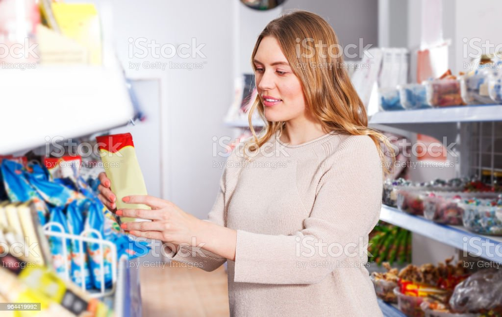 Woman choosing spices in grocery - Royalty-free Business Stock Photo