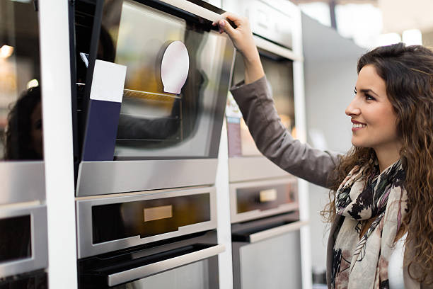 woman choosing stove - happy person buy appliances stock photos and pictures